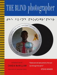 "Cover of ""The Blind Photographer"" featuring images by Tanvir Bush and others, by Julian Rothenstein, introduced by Candia McWilliam and published by Redstone Press. The cover has three horizontal panels in blue, white and red, respectively, and a thin vertical column of yellow and black stripes at the leftmost edge. The white middle panel is the largest and contains a stylised image of a camera lens containing the image of a smiling black man. Above the lens is a text in braille."