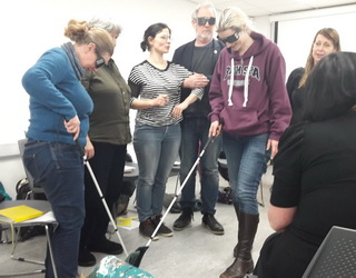 5 Workshop participants, four women and a man, wearing dark glasses, stand in a circle, with Tanvir Bush looking on from behind them. One participant sits with her back to the camera. Two of the standing participants stand arm-in-arm and two are exploring the floor with white canes used by the visually impaired.
