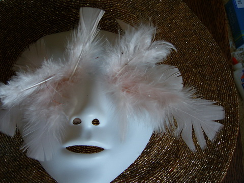 A white plastic mask with soft pink feathers emerging from the eye sockets lies on a flattened gold-beaded wide-brimmed hat.