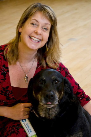 Contact Tanvir Bush and you may hear from Grace as well. Dr. Tanvir Bush, wearing a scarlet dress with black detail, and a silver pendant in the shape of a shell, is smiling up at the camera as she crouches with her arm around her guide dog, black labrador Grace, who helps Tanvir navigate her life. Grace is looking straight at the camera.  Portrait by Penny Ellisanvir Bush Portrait by Penny Ellis