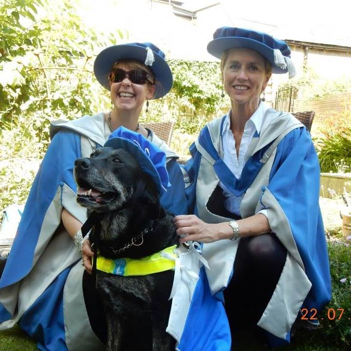 Tanvir Bush and a friend wear blue-and-white graduation gowns and hats as they sit outside in the sunshine with Grace, the guide dog who helps Tanvir to navigate life successfully despite her retinitis pigmentosa. All three of them are smiling!