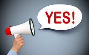 "A hand holds a red-and-white megaphone from which issues a white speech bubble containing the word ""YES!"" in large red letters, used here to convey that the reader must act to comply with the GDPR"